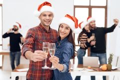 A young couple celebrates at a corporate celebration. They hold glasses with champagne in their hands. They have Santa Claus hats on their heads Stock Images