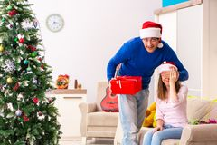 The young couple celebrating christmas at home royalty free stock images