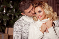 Young couple celebrating New Year at home. Man and woman cuddling on the Christmas tree background Royalty Free Stock Photos