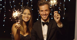 Young couple celebrating new year with sparklers. Elegant romantic young couple celebrating new year with sparklers laughing and smiling against a dark Stock Images
