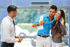 Young Couple Celebrating Purchase of a car In Car Showroom Stock Images