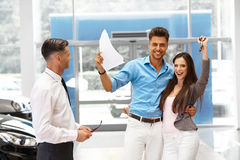 Young Couple Celebrating Purchase of a car In Car Showroom. Royalty Free Stock Photography