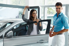 Young Couple Celebrating Purchase of a car In Car Showroom Royalty Free Stock Photos