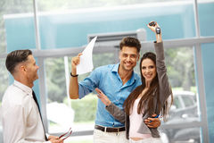 Young Couple Celebrating Purchase of a car In Car Showroom. Royalty Free Stock Image