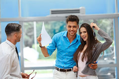 Young Couple Celebrating Purchase of a car In Car Showroom.  Stock Photos