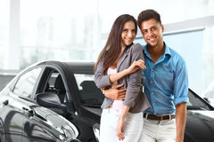 Young Couple Celebrating Purchase of a car In Car Showroom Stock Photography