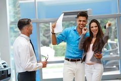 Young Couple Celebrating Purchase of a car In Car Showroom Royalty Free Stock Photography