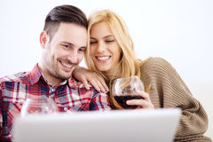 Young couple celebrating with red wine at home Stock Images