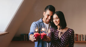 Young couple celebrating their anniversary. Young couple holding two cupcakes and celebrating their anniversary. Cupcakes with sparklers in hands of couple Royalty Free Stock Images