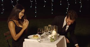 Young couple celebrating Valentines day. Loving young couple celebrating Valentines day dining out at a restaurant with the young woman holding a red wrapped stock footage