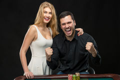 Young couple celebrating win at roulette table in casino. Royalty Free Stock Images