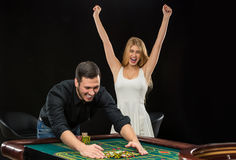 Young couple celebrating win at roulette table in casino. Royalty Free Stock Image