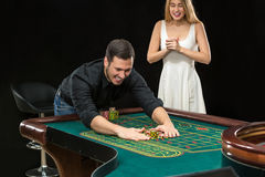Young couple celebrating win at roulette table in casino. Stock Photo