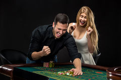Young couple celebrating win at roulette table in casino. Royalty Free Stock Photo