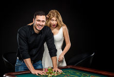 Young couple celebrating win at roulette table in casino. Stock Image