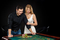 Young couple celebrating win at roulette table in casino. Royalty Free Stock Photography
