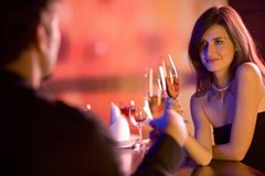 Young couple with champagne glasses in restaurant. Young couple sharing champagne glasses in restaurant, celebrating or on romantic date. Focus on woman Stock Photos