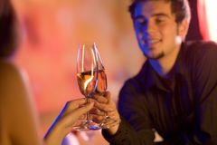 Young couple with champagne glasses in restaurant. Young couple sharing champagne glasses in restaurant, celebrating or on romantic date. Focus on glasses Stock Image