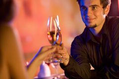 Young couple with champagne glasses in restaurant Royalty Free Stock Photography