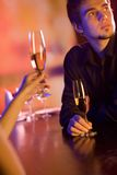 Young couple with champagne glasses in restaurant. Young couple sharing champagne glasses in restaurant, celebrating or on romantic date. Focus on man Royalty Free Stock Photography