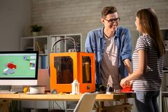 Young Couple Chatting in Design Studio. Portrait of young men and women smiling and chatting standing at desk with modern PC and 3d printer while working in stock images