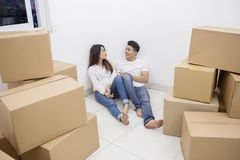 Young couple chatting in the new apartment. Picture of young couple chatting together while sitting near stacks of cardboard boxes in the new apartment stock image