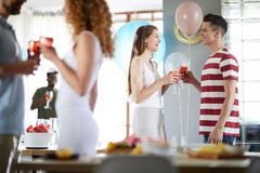 Young Couple Chatting at Party. Side view portrait of young couple chatting while enjoying party indoors, copy space stock photos