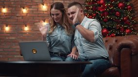 Young couple chatting with relatives via webcam stock footage