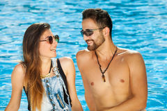 Young couple chatting at the side of a pool. Stock Photos