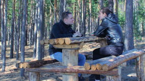 Young couple chatting smiling having rest in beautiful autumn forest. Young happy couple chatting smiling having rest in beautiful autumn forest stock video