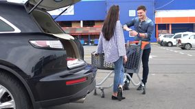 Young couple chatting in a store parking lot stock video