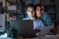 Young couple checking bills at night Stock Images