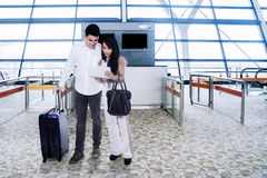 Young couple checking flight information on tablet Royalty Free Stock Photos
