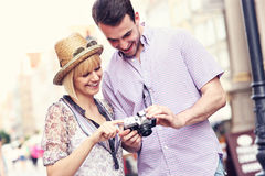 Young couple checking pictures on their camera Royalty Free Stock Image