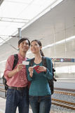 Young Couple Checking The Train Schedule Royalty Free Stock Image