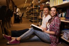 Young couple of cheerful students sitting on the floor and studying in the university  library. Stock Images