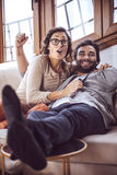 Young couple cheering for a sport team watching sports on TV Stock Images