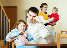 Young couple with children after quarrel at home Royalty Free Stock Photos