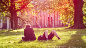 Young couple chill on the meadow in evening sunlight in front of Bruehl`s Terrace or The Balcony of Europe. Colorful stock images