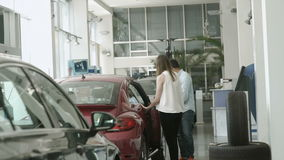 Young couple choose the modern car in car dealership. In love couple is choosing the automobile in car dealership. Young girl come to red car and open the door stock footage