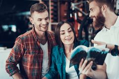 Young Couple Choose New Bicycle with Consultant. Smiling Man and Happy Woman Look Attentively at Instruction or Catalog with Different Bikes and Details. The royalty free stock photos