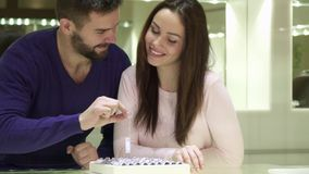 Young couple chooses engagement rings at the jewelry shop. Young caucasian couple choosing engagement rings at the jewelry shop. Pretty brunette girl pointing Royalty Free Stock Photos