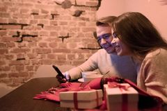 Young Couple Chooses Gifts in the Phone via the Internet stock photography