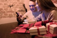 Young Couple Chooses Gifts in the Phone via the Internet stock images