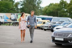 A young couple chooses their first car. Lovers walk around the caravan and look at cars.q. Beautiful young couple standing at the dealership choosing the car to Stock Images