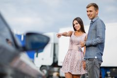 A young couple chooses their first car. Lovers walk around the caravan and look at cars.q royalty free stock photos
