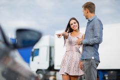 A young couple chooses their first car. Lovers walk around the caravan and look at cars.q. Beautiful young couple standing at the dealership choosing the car to Royalty Free Stock Image
