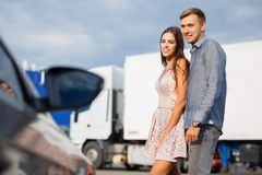 Young couple chooses used car in the street showroom. Stock Images