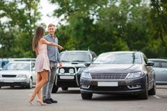 Young couple chooses used car in the street showroom. Stock Photos