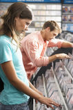 Young couple choosing CD`s in record shop, side view Royalty Free Stock Photography